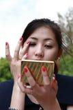 De jonge vrouw kijkt in spiegel en maakt omhoog ogeninkt Royalty-vrije Stock Afbeelding