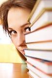 De jonge vrouw kijkt uit van voor stapels van boeken Stock Afbeeldingen