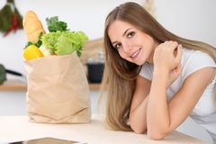 De jonge vrouw is klaar voor het koken in een keuken Het grote document zakhoogtepunt van verse groenten en vruchten bevindt zich Royalty-vrije Stock Fotografie