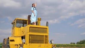 De jonge vrouw in kleding bevindt zich op gele tractor en golvend Hello in langzame motie op blauwe hemel als achtergrond stock video