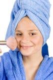 De jonge vrouw kleedde blauwe badjas zettend gezicht-poeder Royalty-vrije Stock Afbeeldingen