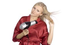 De jonge vrouw kleedde rode badjas gebruikend haardroger Stock Foto's