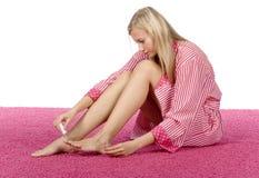 De jonge vrouw kleedde roze/witte badjas het schilderen spijkers Stock Afbeeldingen