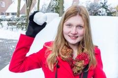 De jonge vrouw kleedde zich in rode holdingssneeuwbal stock afbeelding