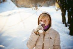 De jonge vrouw kleedde zich in warme kleren drinkend meeneemkoffie Stock Afbeeldingen