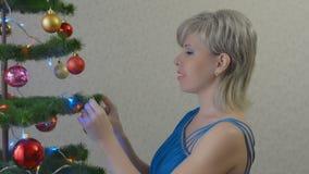 De jonge vrouw kleedt de Kerstboom stock footage