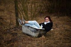 De jonge vrouw in kleren neemt een leeg oud bad in het midden van een bos stock fotografie