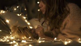 De jonge vrouw koestert en kust haar hond omringde Kerstmislichten op bed stock videobeelden