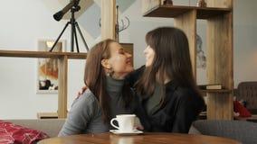 De jonge vrouw komt in de koffie voor twee vrienden samen die een kop van koffie drinken Drie meisjes komen in koffie samen stock footage