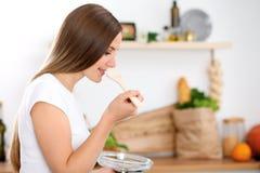 De jonge vrouw kookt in een keuken De huisvrouw proeft de soep door houten lepel Royalty-vrije Stock Afbeelding