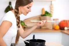 De jonge vrouw kookt in een keuken De huisvrouw proeft de soep door houten lepel Royalty-vrije Stock Fotografie
