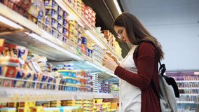 De jonge vrouw koopt de kaas in de supermarkt stock videobeelden