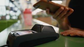 De jonge vrouw koopt iets en verricht betaling met smartphone stock footage