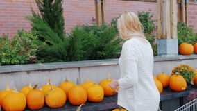 De jonge vrouw koopt pompoenen in Halloween Amerikaanse tradities en het feestelijke winkelen stock video