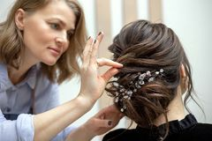 De jonge vrouw krijgt een kapsel bij een salon stock afbeeldingen