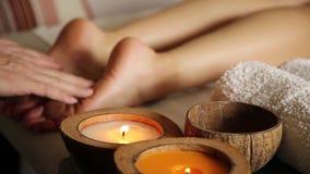 De jonge vrouw krijgt een voetmassage in de kuuroordsalon Close-up van kaarsen mannelijke handendia op de vrouwelijke benen stock video