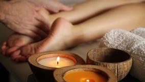 De jonge vrouw krijgt een voetmassage in de kuuroordsalon Close-up van kaarsen mannelijke handendia op de vrouwelijke benen stock videobeelden