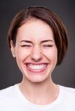 De jonge vrouw lacht luid Royalty-vrije Stock Afbeeldingen