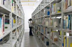 De jonge vrouw leest in doorgangen in een openbare bibliotheek stock afbeeldingen