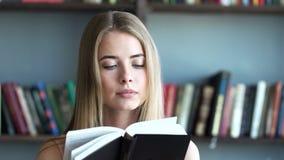 De jonge vrouw leest een literatuur of het leren stock video