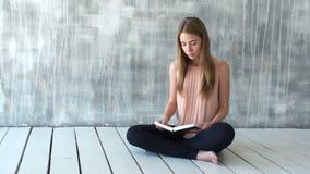 De jonge vrouw leest een literatuur of het leren stock videobeelden