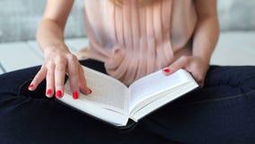De jonge vrouw leest een literatuur of het leren stock footage