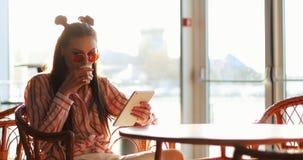 De jonge vrouw leest iets in haar lijsten die bij de lijst in koffie buiten zitten stock video