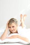 De jonge vrouw legde op een bed Stock Foto