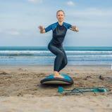 De jonge vrouw leidt om zich op de branding vóór de eerste het surfen les te bevinden op royalty-vrije stock fotografie