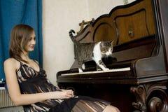 De jonge vrouw let op kat lopend op piano Stock Fotografie