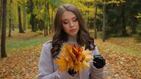 De jonge vrouw in liefde, met een bos van gele bladeren, wacht haar honing in een park, stock video