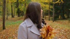 De jonge vrouw in liefde, met een bos van gele bladeren, zoekt haar honing in een park, stock videobeelden