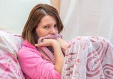 De jonge vrouw ligt in bed Royalty-vrije Stock Afbeelding