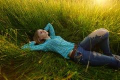 De jonge vrouw ligt in het hoge gras Stock Afbeeldingen