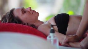 De jonge vrouw ligt in kuuroordzaal het ontspannen op het tropische strand Sluit omhoog van massagetherapeut die handenmassage do stock videobeelden