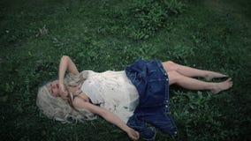 De jonge vrouw ligt op het gras stock footage