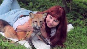 De jonge vrouw ligt in openlucht op gras in park met rode vos stock footage