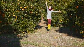 De jonge vrouw loopt in de oranje tuin stock videobeelden