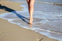 De jonge vrouw loopt dichtbij overzees in een de zomerochtend Sluit omhoog foto van benen Stock Afbeelding