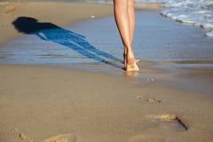 De jonge vrouw loopt dichtbij overzees in een de zomerochtend Sluit omhoog foto van benen Stock Foto's