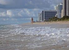De jonge vrouw loopt het Strand van Miami in de ochtend Royalty-vrije Stock Afbeeldingen