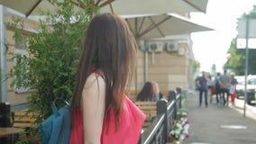 De jonge vrouw loopt langs straat in de zomerdag stock video