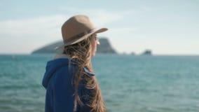 De jonge vrouw loopt langs strand in hoed en bekijkt camera en rond stock video