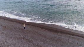 De jonge vrouw loopt op overzeese kust met het bespatten van golven Lucht Mening stock video