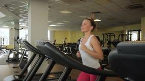 De jonge vrouw loopt op tredmolen bij sportclub Vrouwelijke Jogging stock videobeelden
