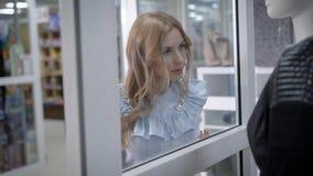 De jonge vrouw loopt over zaal in het uitwisselen van wandelgalerij in dag, lettend op een ledenpop in een showcase van kledingsw stock video