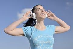 De jonge vrouw luistert aan muziek Stock Fotografie