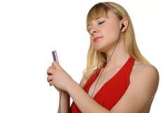 De jonge vrouw luistert aan muziek van een speler Royalty-vrije Stock Foto's