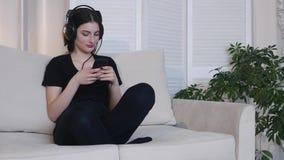 De jonge vrouw luistert thuis aan muziekzitting op bank 4K stock videobeelden