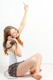 De jonge vrouw luistert vreugdevol aan audio Stock Foto